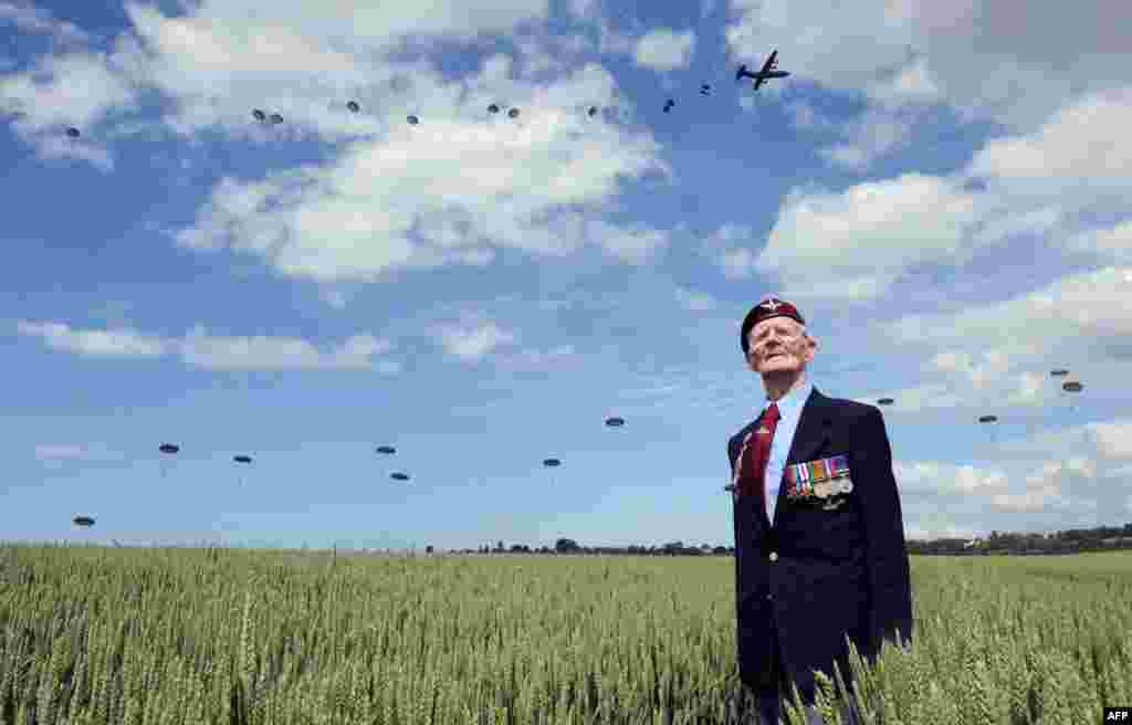 British World War II veteran Frederick Glover looks at soldiers parachuting down during a D-Day commemoration in Ranville, northern France, on the eve of the 70th anniversary of the World War II Allied landings in Normandy.