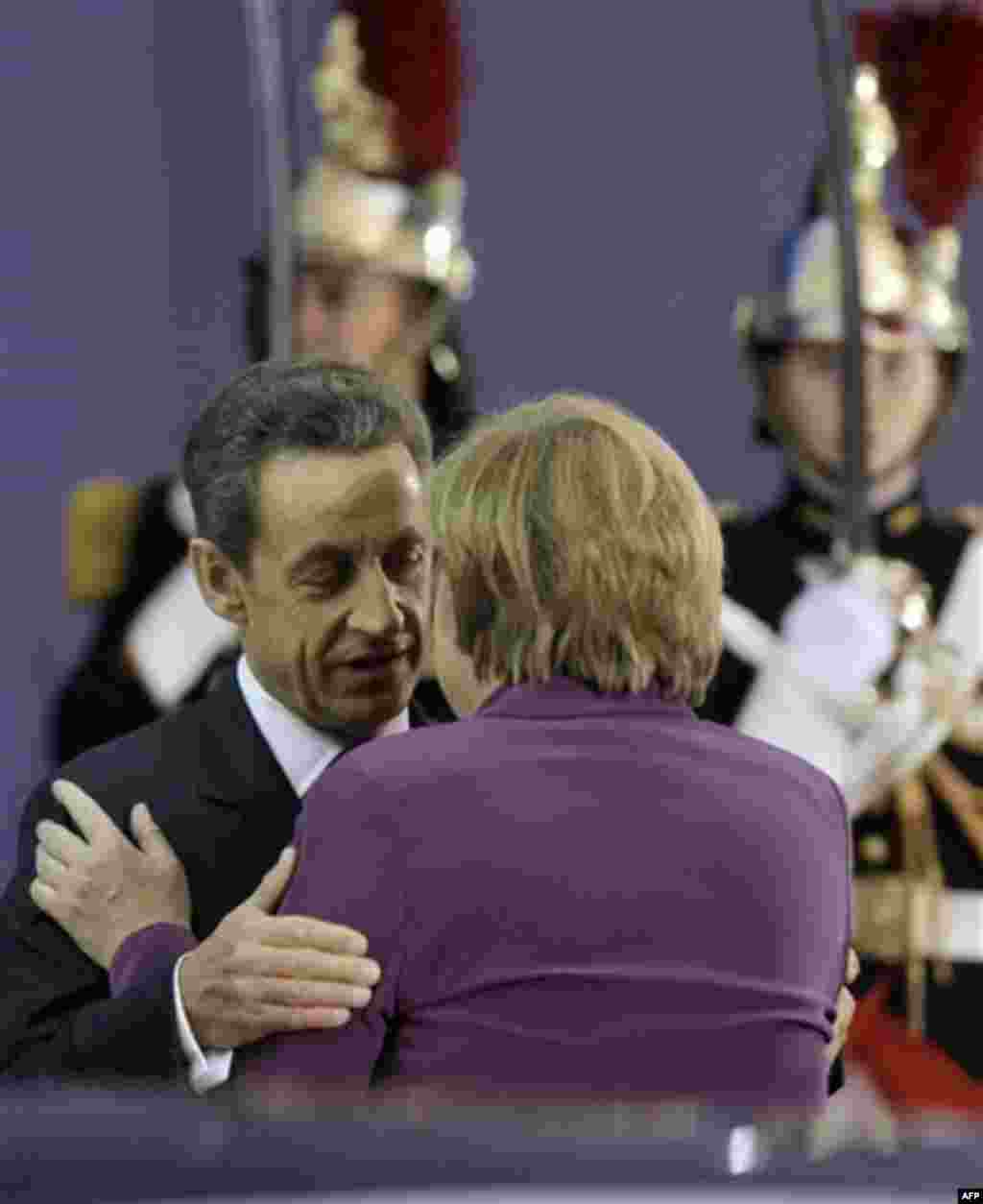 French President Nicolas Sarkozy, left, greets German Chancellor Angela Merkel during arrivals for the G20 summit in Cannes, France on Wednesday, Nov. 2, 2011. Greek Prime Minister George Papandreou was flying to the chic French Riviera resort of Cannes