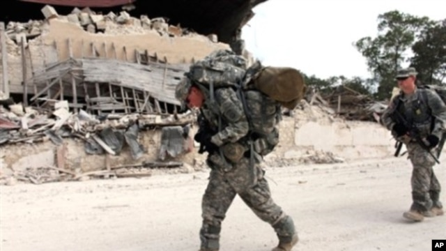 US soldiers of the 82nd Airborne Division walk in streets after leaving the Presidential palace en route to the general hospital in downtown Port-au-Prince, 19 Jan 2010