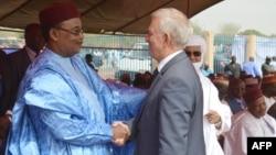 Le président Mahamadou Issoufou du Niger salue Michel Roussin à l'occasion de l'inauguration d'un tronçon ferroviaire de 140 km construit par le groupe français Bolloré et qui reliera à terme Niamey à Cotonou, le 29 janvier 2016.