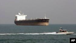 FILE - An Iranian Revolutionary Guard speedboat passes near an oil tanker, July 2, 2012.