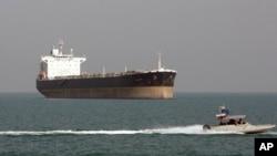 Arhiva - Gliser Iranske revolucionarne garde prolazi ispred tankera za prevoz nafte, 2. jula 2012.
