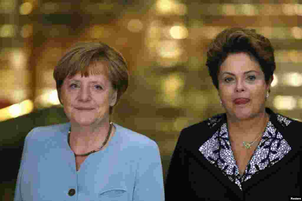 Brazilian President Dilma Rousseff (right) receives German Chancellor Angela Merkel who is in Brazil to attend the upcoming Germany v. Portugal 2014 World Cup game, in Brasilia, June 15, 2014.