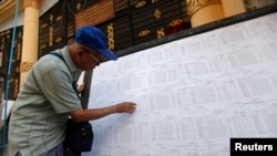 A man searches for his name through lists of voters outside an election commission office in Yangon November 4, 2010. Myanmar will hold its first parliamentary election in two decades on November 7, although critics say it will simply cement the military'