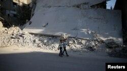 12일 시리아 수도 다마스쿠스 인근 반군장악 지역에서 무너져내린 건물 앞으로 어린이들이 걸어가고 있다.
