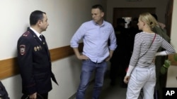 Russian opposition leader Alexei Navalny, center, and his wife Yulia talk before a hearing in a court in Moscow, Russia, on June 12, 2017.