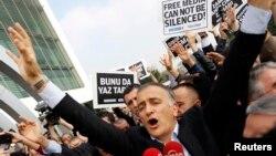 Reaksi pemimpin redaksi Zaman, Ekrem Dumanli, dikelilingi oleh koleganya dan petugas polisi (tengah), saat meninggallkan kantor harian Zamandi Istambul 14 Desember 2014.