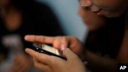 Tinejdžerka iz Indonezije proverava poruke na telefonu (Foto: AP/Dita Alangkara)