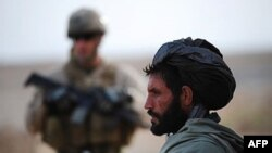 An Afghan farmer watches as U.S. Marines on the outskirts of Marjah in central Helmand, 26 Jan 2010