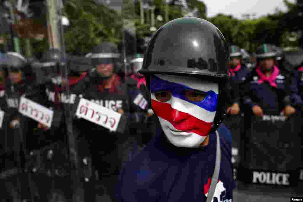 An anti-government protester wearing a mask painted in the colors of the Thai national flag looks on as riot police officers stand guard outside the parliament in Bangkok. Thailand's parliament was due to debate a political amnesty bill as anti-government protesters marched to try to get it scrapped, saying it could let ex-premier Thaksin Shinawatra return from exile without having to serve a jail sentence.