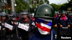 FILE - An anti-government protester wearing a mask painted in the colors of the Thai national flag looks on as riot police officers stand guard outside the parliament in Bangkok, Aug. 7, 2013.