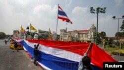 Para demonstran anti-pemerintah membungkus pintu gerbang dan pagar di sekeliling Wisma Pemerintah Thailand di Bangkok dengan spanduk raksasa berhias warna-warna bendera Thailand (13/12).