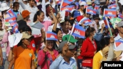 Garment workers shout and wave Cambodian national flags as they take part in a protest calling on the government to raise wages during a march to mark Labour Day in Phnom Penh May 1, 2015. (REUTERS/Samrang Pring)