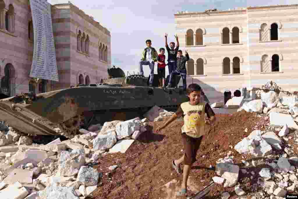 2012年10月8日在敘利亞北部靠近土耳其邊界的阿扎茲城,效忠敘利亞總統阿薩德的部隊一輛遭受毀壞的裝甲運兵車。儿童在車輛週邊玩耍。(路透社)