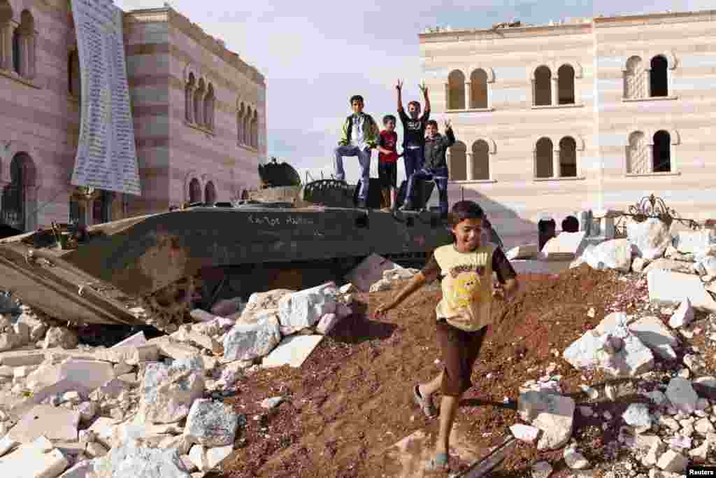 8일 시리아 북부 터키 접경지역인 아자즈 시의 아이들. 바샤르 알 아사드 대통령 친위부대의 부서진 장갑차 주변에서 놀고 있다.