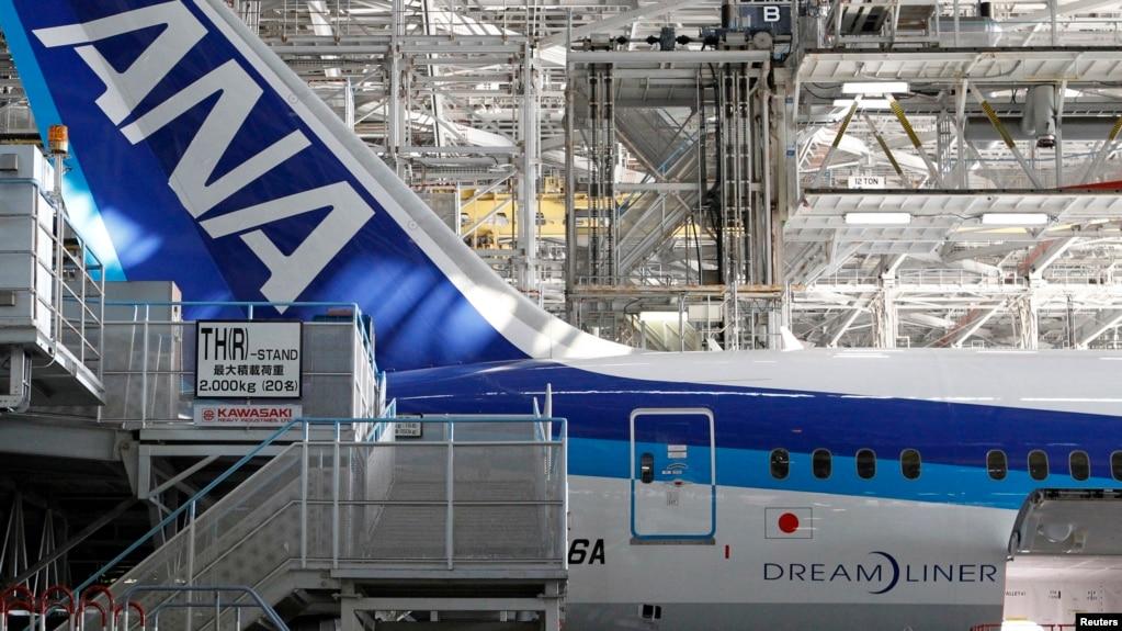 2013年4月28日,在全日空航空公司(ANA)的波音787夢幻客機下面,人們從事維修工作。