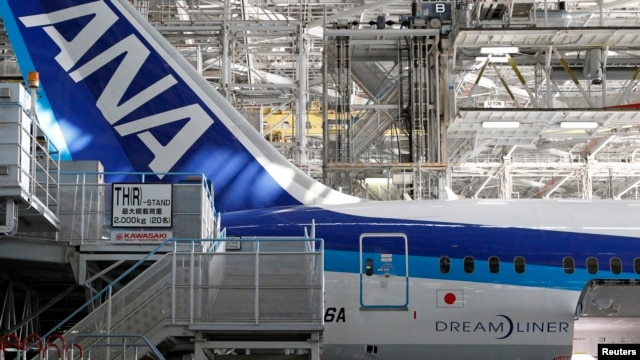 FILE - People work under an All Nippon Airways' (ANA) Boeing Co's 787 Dreamliner aircraft at ANA's maintenance center.