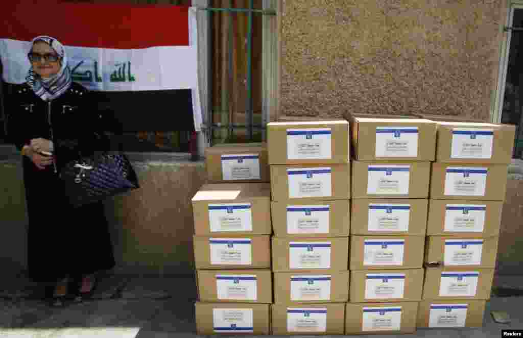 An employee of Iraq's Independent High Electoral Commission (IHEC) stands beside stacks of polling station kits during preparations for the provincial elections, in Baghdad April 19, 2013.