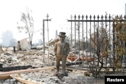 A statue stands among the remains of a home destroyed by the Tubbs Fire in Santa Rosa, Calif., Oct. 10, 2017.