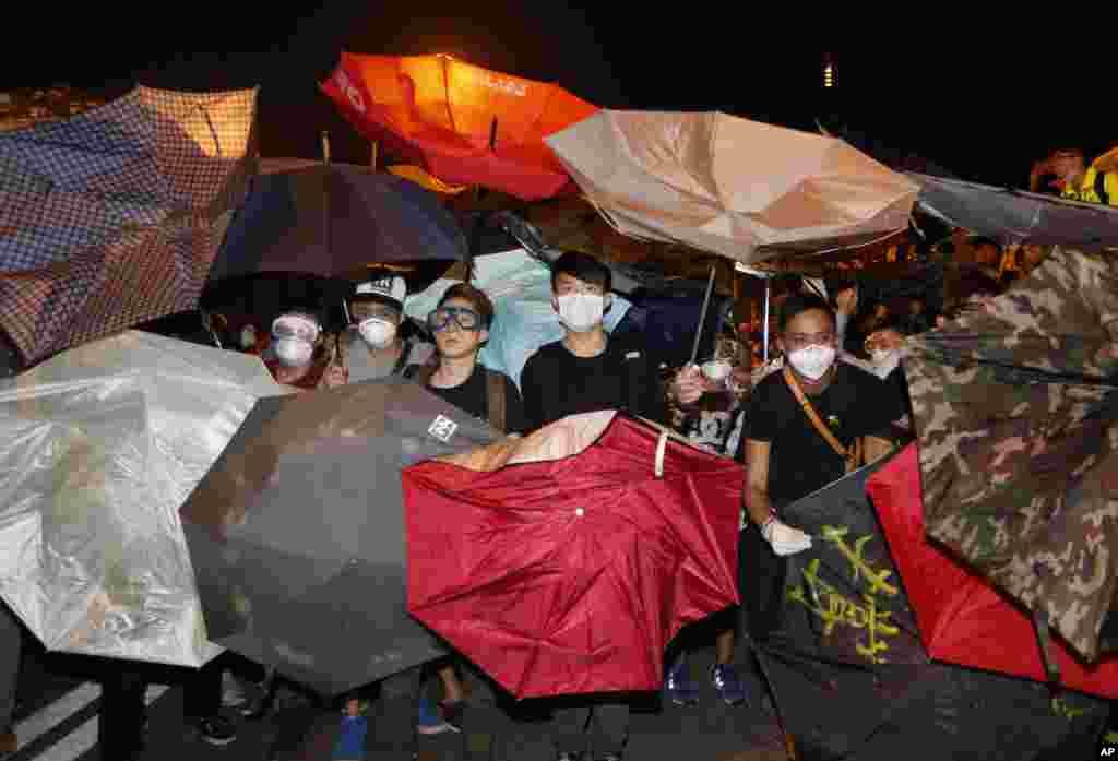 Para demonstran menggunakan payung untuk menghindari air merica yang disemprotkan oleh polisi di luar kantor-kantor pemerintahan Hong Kong di daerah Admiralty (15/10). (AP Photo/Kin Cheung)