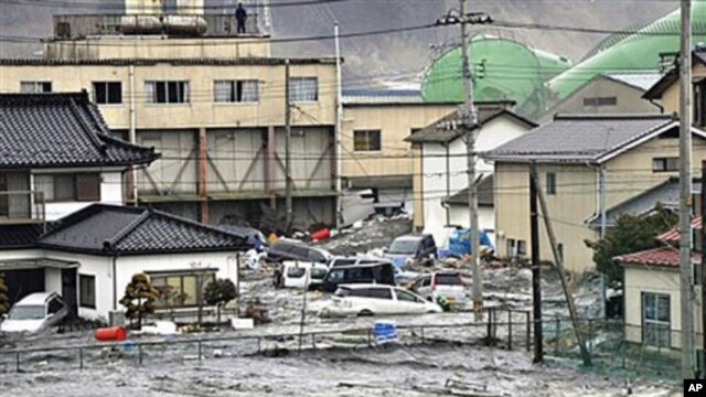 An earthquake-triggered tsunami washes away a warehouse and vehicles in Kesennuma, Miyagi prefecture (state), Mar 11 2011