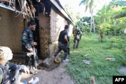 FILE - Police and soldiers take up positions as they engage with the Abu Sayyaf group in the village of Napo, Inabanga town, Bohol province, in the central Philippines, April 11, 2017.