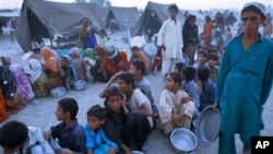 Pakistani children wait for cooked food at a camp for people displaced by floods in Sukkur, southern Pakistan. Government officials organized an event to entertain flood affected people and help them temporarily forget life at the camps, 21 Sep 2010.