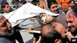 بم دھماکے کے بعد لوگ مولانا شوکت شاہ کی میت لے جاتے ہوئے