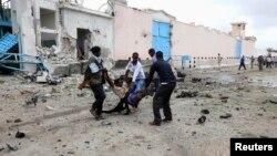 2013年6月19日,摩加迪沙一處聯合國大院遭到自殺炸彈襲擊後,索馬利亞政府軍士兵把一名受傷的人轉移出大院。