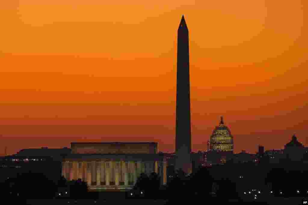 The orange sky of sunrise is captured behind the skyline of Washington on the first day back to work for the U.S. Congress after their summer recess.