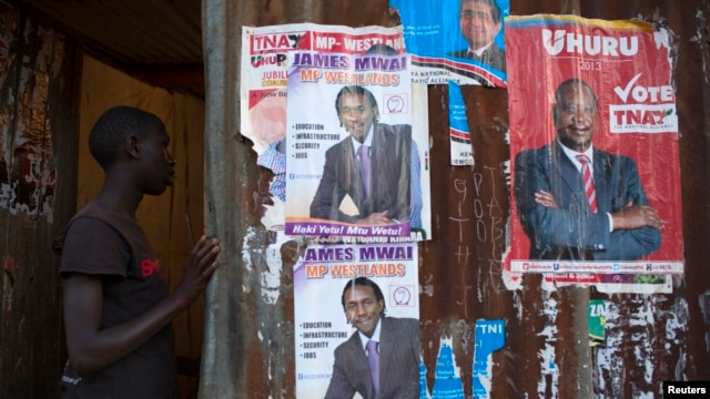 A boy enters an house with various campaign posters at the Kangemi slum in Kenya's capital Nairobi, February 28, 2013.