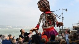 Engleski glumac <strong>Džud Lou</strong> drži ruku &quot;Male Amal&quot;, džinovske lutke koja predstavlja&nbsp;devojčicu izbeglicu iz Sirije, dok se šesta duž obale mora u luci Folkestoun, na jugoistoku Engleske, gde je stigla iz Kalea, u sklopui međunarodnog umetničkog projekta &quot;Šetnja&quot; (The Walk) (Foto: AFP/Glyn Kirk)