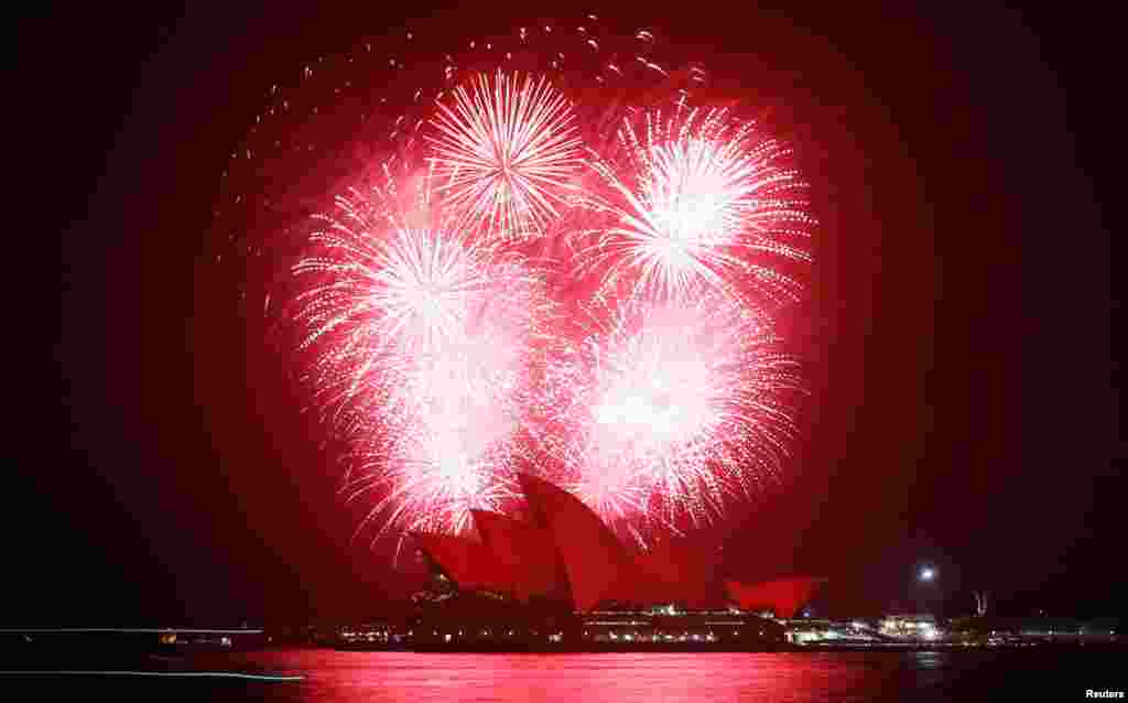 Fireworks explode over the Sydney Opera House, November 30, 2012, as it is bathed in red light to mark World AIDS Day.