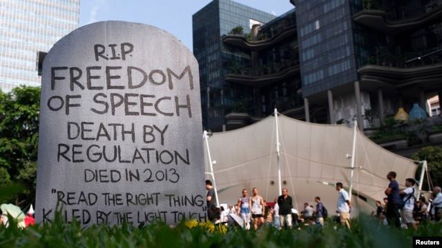 Protesters walk past a mock gravestone that reads 'RIP Freedom of Speech' during a protest against new licensing regulations imposed by the government for online news sites, at Hong Lim Park in Singapore, June 8, 2013.