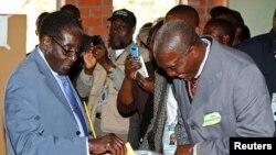 Presiden Zimbabwe Robert Mugabe (kiri) memberikan suaranya pada pemilihan umum di Harare (31/7).