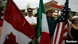 FILE - A resident holds the flags of Canada, Mexico and the U.S.