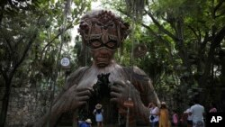 "Wisatawan menunggu giliran untuk berfoto dengan patung figuratif yang berfungsi sebagai gapura karya seniman Afrika Selatan Daniel Popper berjudul, ""Ven a la Luz"" di resor Ahau Tulum, negara bagian Quintana Roo, Meksiko, Senin, 4 Januari, 2021. (AP Photo/Emilio Espejel)"