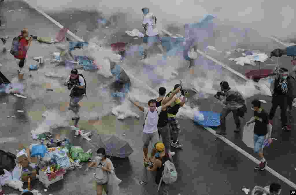 Protesters walk through tear gas used by riot police after thousands of people blocked a main road at the financial central district in Hong Kong.