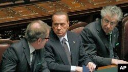 Italian PM Silvio Berlusconi (C) speaks with Justice Minister Roberto Maroni (R) and League North Party leader Umberto Bossi during a finance vote at the parliament in Rome, November 8, 2011