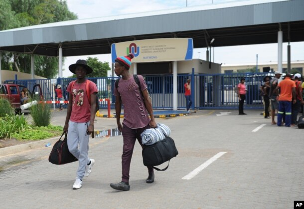 FILE - Students leave the campus at the North-West University in Mahikeng, South Africa, (also known as Mafikeng) Feb. 25, 2016, after protesting students burned down parts of the campus.