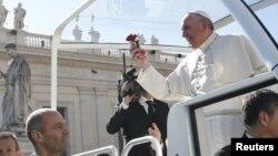 Paus Fransiskus memegang bunga pemberian seorang umat Katolik, dalam sebuah acara di Lapangan Santo Petrus, Vatikan (foto: dok).