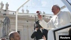 Le pape François tient une fleur jetée par un fidèle, à son arrivée à une audience spéciale avec les fiancés, pour célébrer le jour de la Saint-Valentin, sur la Place Saint-Pierre au Vatican, le 14 février 2014.