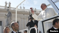 FILE: Pope Francis holds a flower thrown by a faithful as he arrives to lead a special audience with engaged couples, to celebrate Saint Valentine's day, in Saint Peter's Square at the Vatican, Feb. 14, 2014.