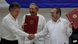 Colombian President Juan Manuel Santos, left, and FARC Commander Timoleon Jimenez shake hands during a signing ceremony of a cease-fire and rebel disarmament deal, in Havana, Cuba, June 23, 2016. Pictured in the center is Cuba's President Raul Castro.