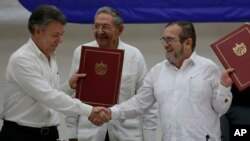 FILE - Colombian President Juan Manuel Santos, left, and Timoleon Jimenez, commander of the Revolutionary Armed Forces of Colombia, or FARC, shake hands during a signing ceremony of a cease-fire and rebel disarmament deal, in Havana, Cuba, June 23, 2016.