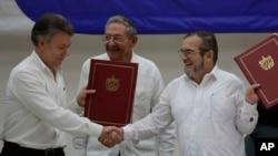 후안 마뉴엘(왼쪽) 콜롬비아 대통령과 티몰레온 히메네즈 콜롬비아 무장혁명군(FARC) 사령관이 23일 쿠바 수도 아바나에서 휴전협정문에 서명한 뒤 악수하고 있다.