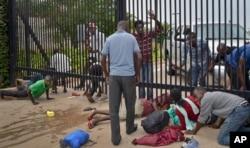 Student protesters seeking refuge crawl under the gates of the U.S. Embassy in the capital Bujumbura, Burundi, June 25, 2015.