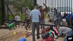 Student protesters seeking refuge crawl under the gates of the U.S. Embassy in the capital Bujumbura, Burundi, June 25, 2015.