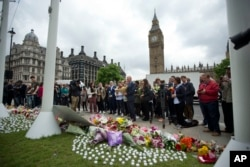 Staff from Britain's opposition Labour Party stand together before placing floral tributes for their colleague Jo Cox, the 41-year-old British Member of Parliament shot to death yesterday in northern England, on Parliament Square outside the House of Parliament in London, Friday, June 17, 2016.