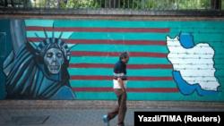 Čovjek prolazi protiv anti-Američkog murala u Teheranu.